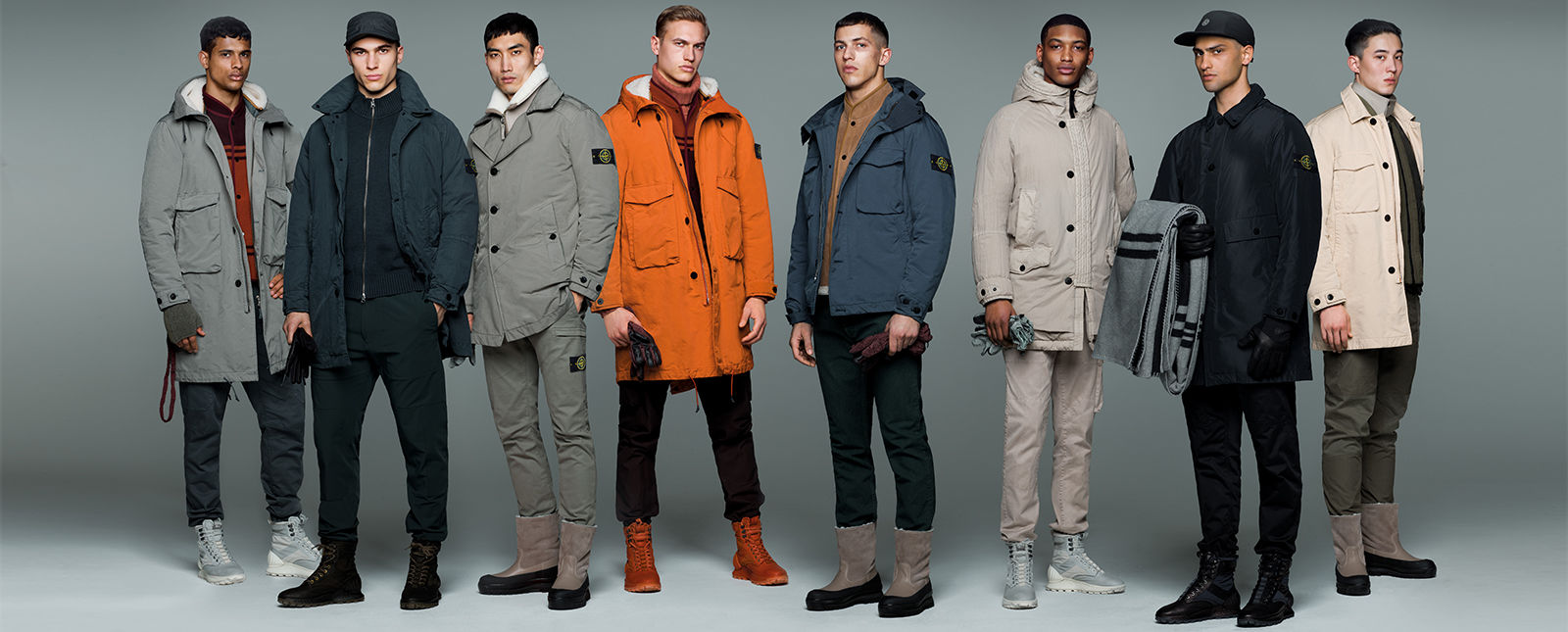 Eight models wearing Stone Island jackets in different colors and styles.