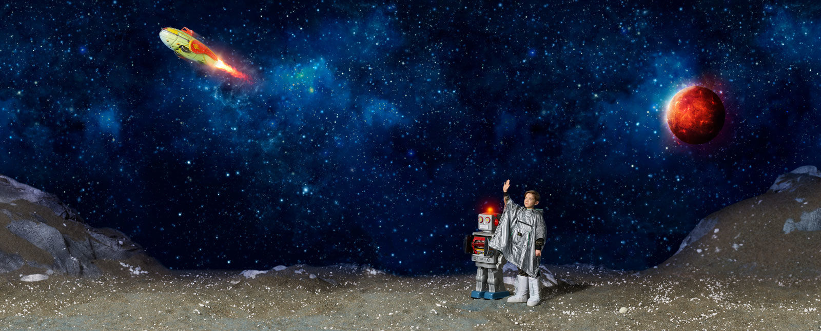 Faraway planet landscape with robot next to junior model wearing silver anorak and space boots waving at passing spaceship.