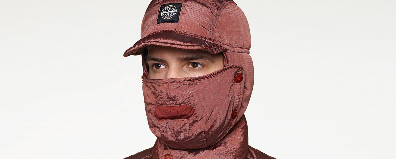 Close up of model wearing hood with visor and face guard in faded red nylon fabric.