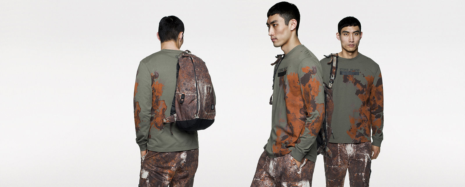 Back, side and front view of model in green, long sleeve T shirt with brown and orange print, carrying a backpack on his shoulder.