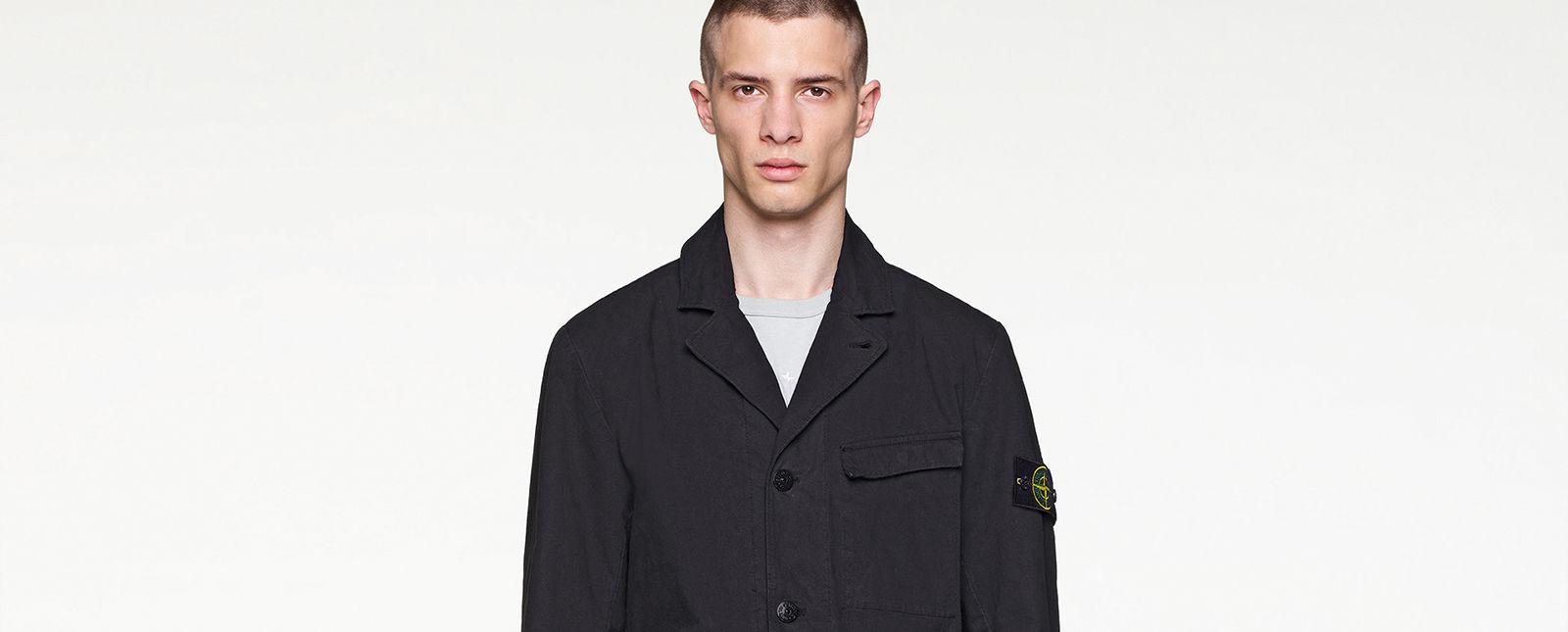 Model wearing black, single breasted jacket with Stone Island badge on left arm.