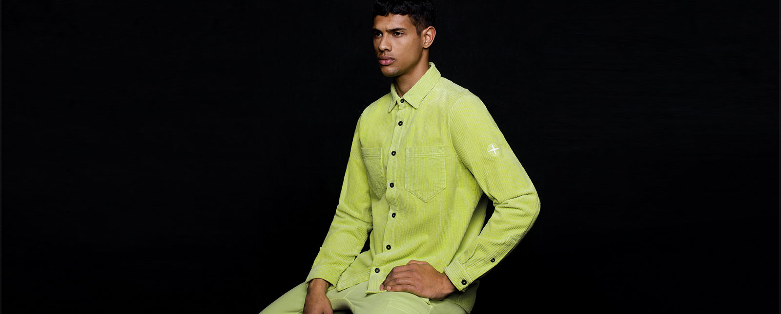 Model wearing lime green shirt with patch pockets at chest and button closure.