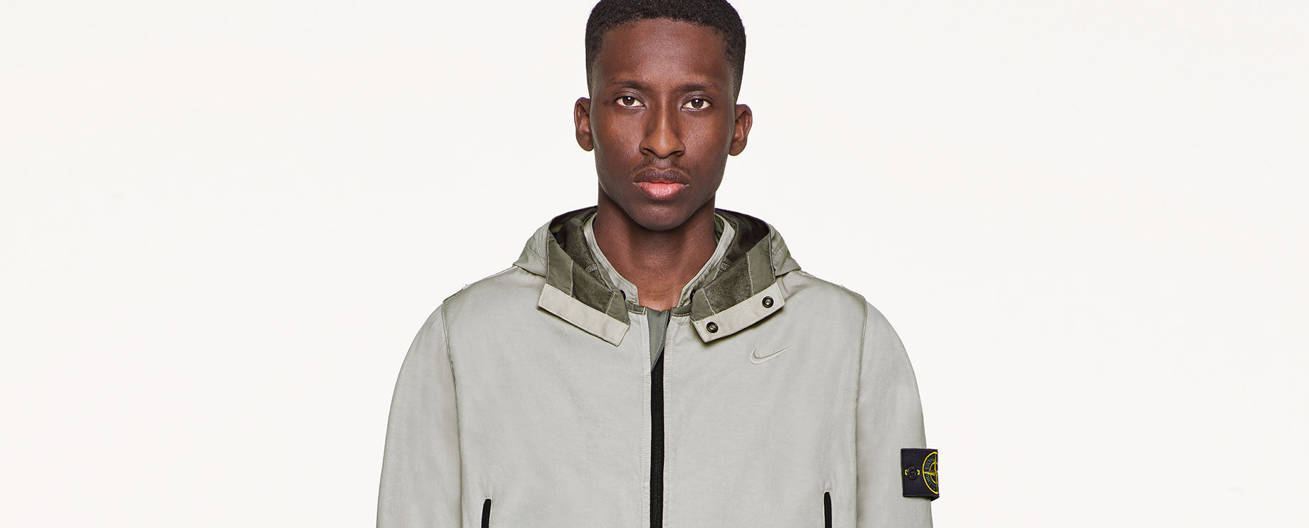 Model wearing gray, performance jacket with hood and Stone Island badge on left arm.