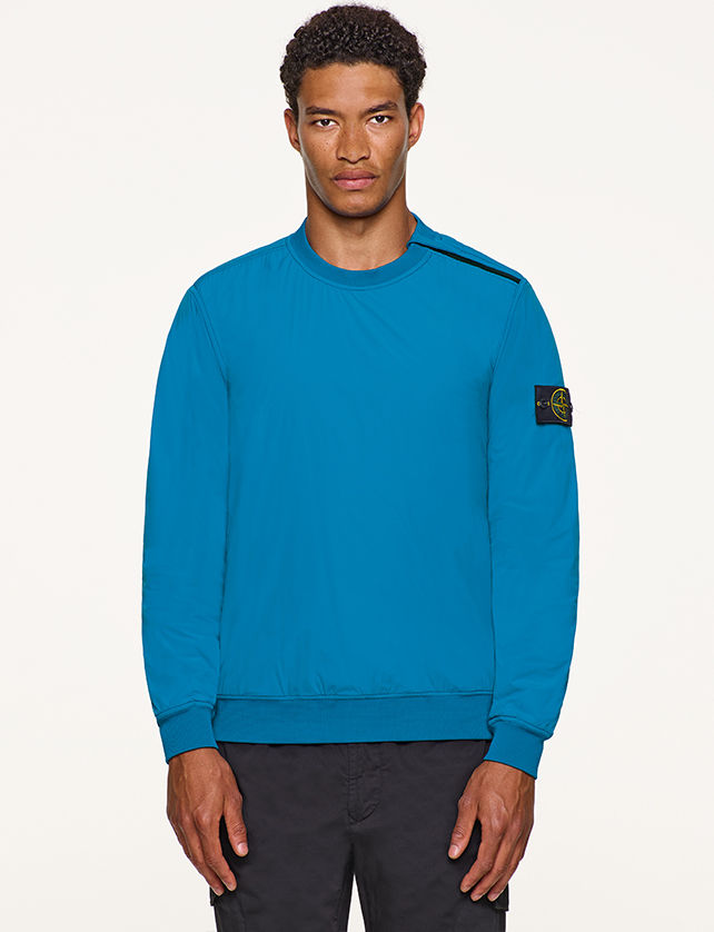 Model wearing turquoise, performance crewneck top with Stone Island badge on left arm.