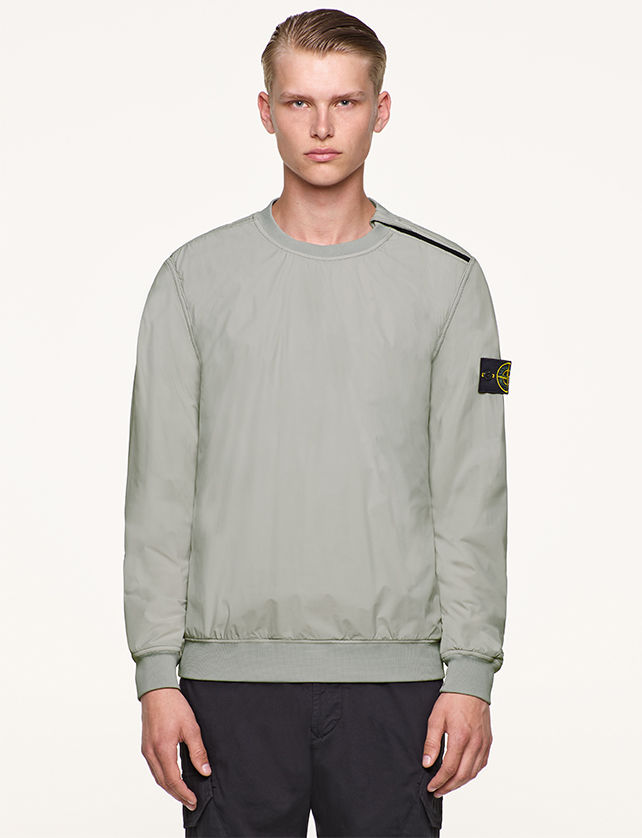 Model wearing gray, performance crewneck top with Stone Island badge on left arm.