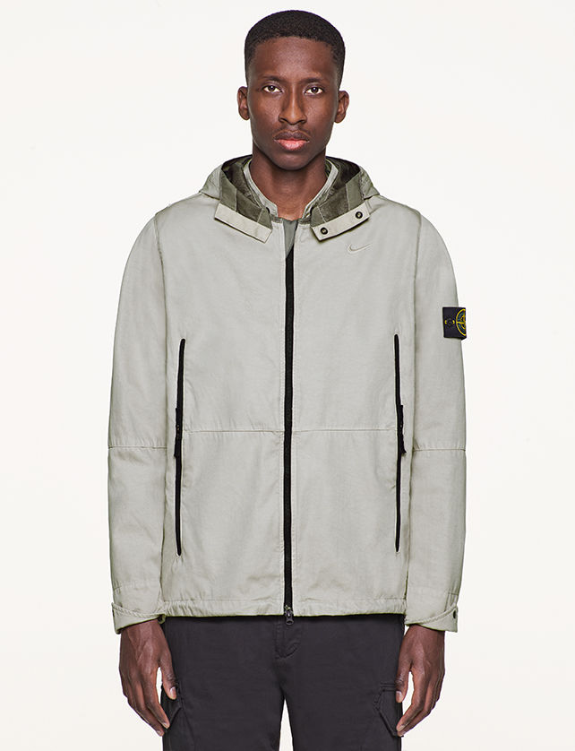 Model wearing gray, performance jacket with hood, vertical, black zipper pockets and black zipper fastening.