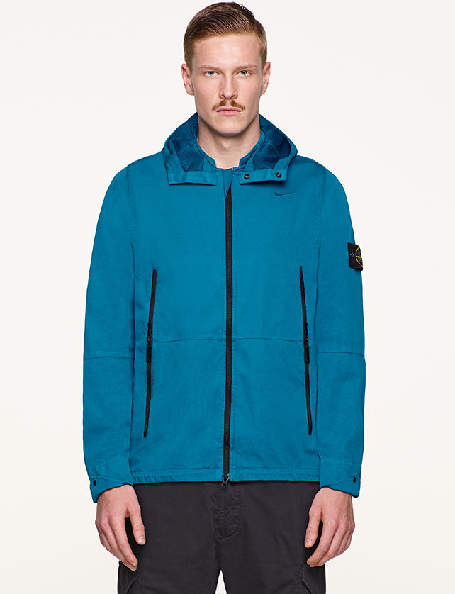 Model wearing turquoise, performance jacket with hood, vertical, black zipper pockets and black zipper fastening.