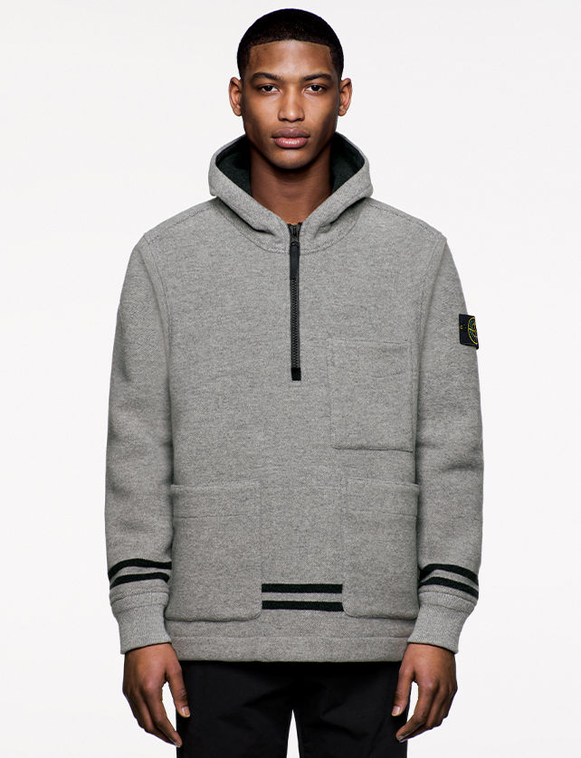 Model wearing gray, hooded sweatshirt with black stripes, two horizontal pockets and a third at left chest and zipper fastening at chest.