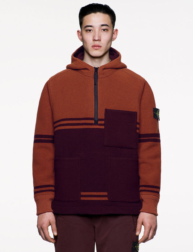 Model wearing black and brown, hooded sweatshirt with two horizontal pockets and a third at left chest and zipper fastening at chest.
