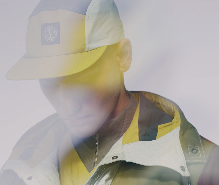 Close up of model wearing multicolored jacket and matching cap wit Stone Island patch.