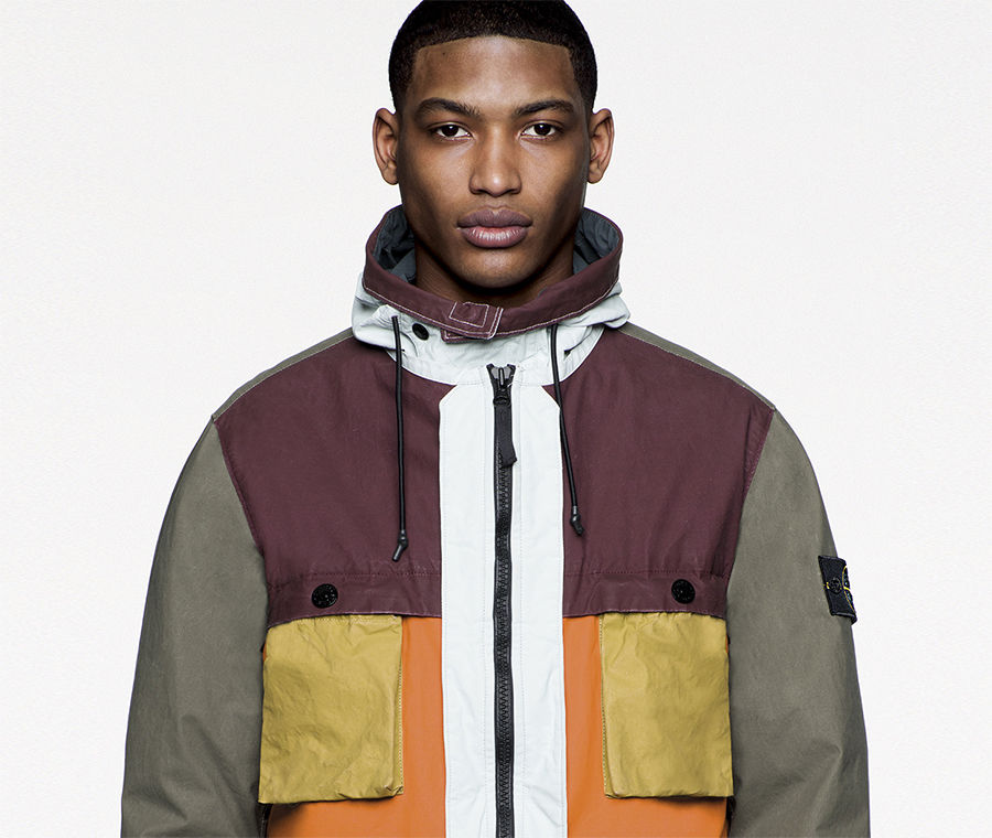 Model wearing multicolored jacket with black zipper fastening and Stone Island badge on left arm.