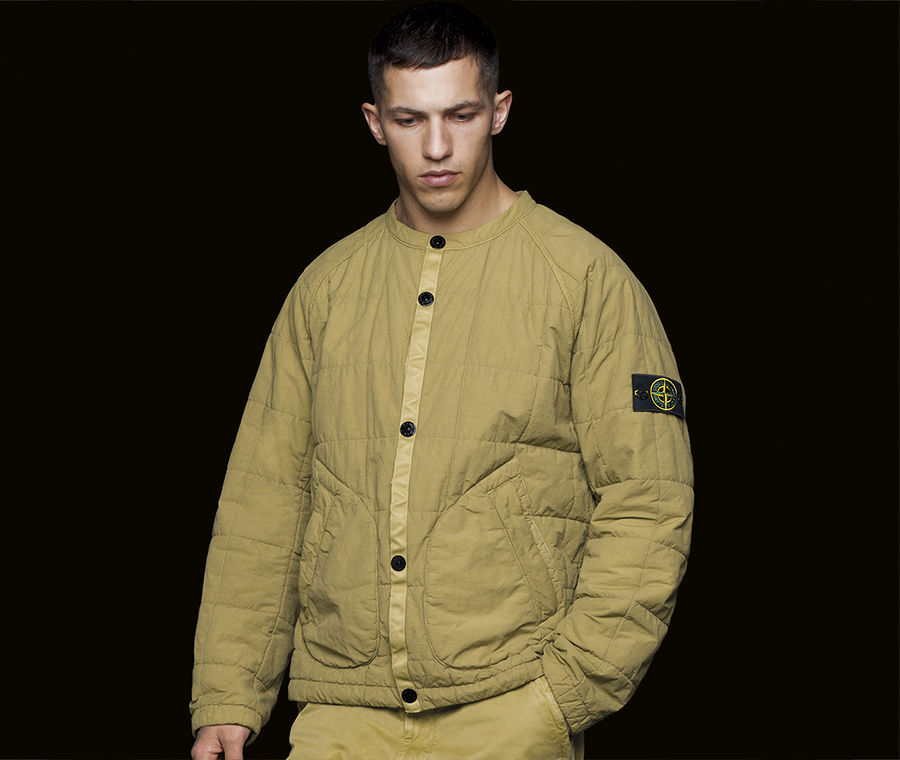 Model wearing jacket in quilted, mustard fabric, with Stone Island badge on left arm.