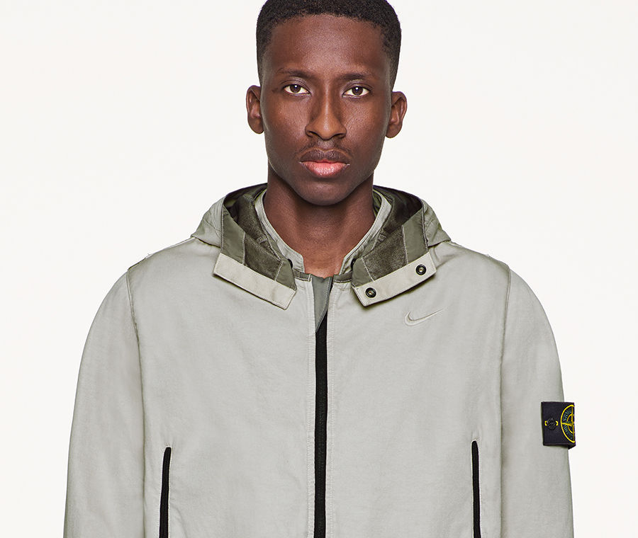 f95e6768acf0 Model wearing gray, performance jacket with hood and Stone Island badge on  left arm.