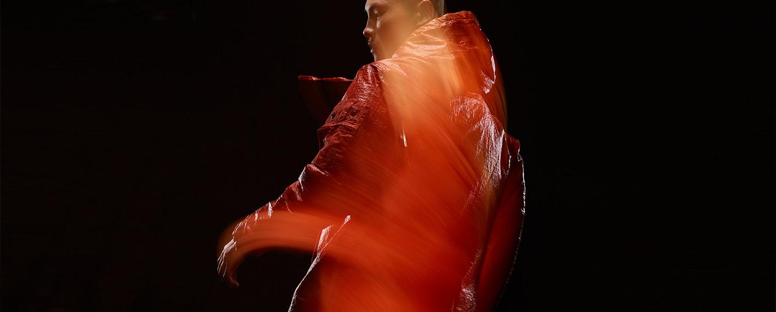 Blurred shot of model wearing red, hooded jacket.