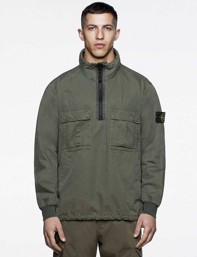 Model wearing green anorak with bellows pockets at chest and a black zipper closure at chest.