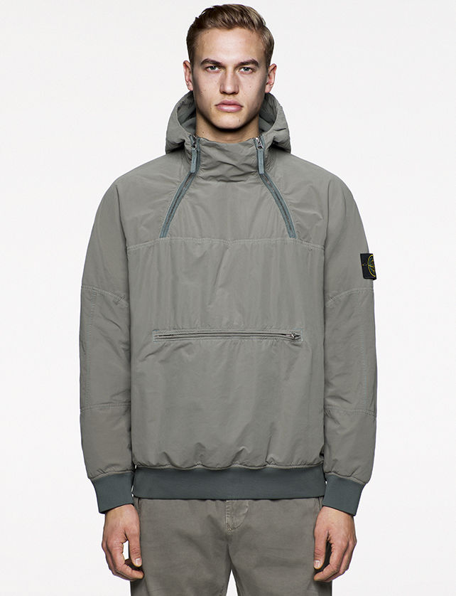 Model wearing gray, hooded anorak with a central, horizontal pocket with zipper closure and two diagonal zippers at chest.