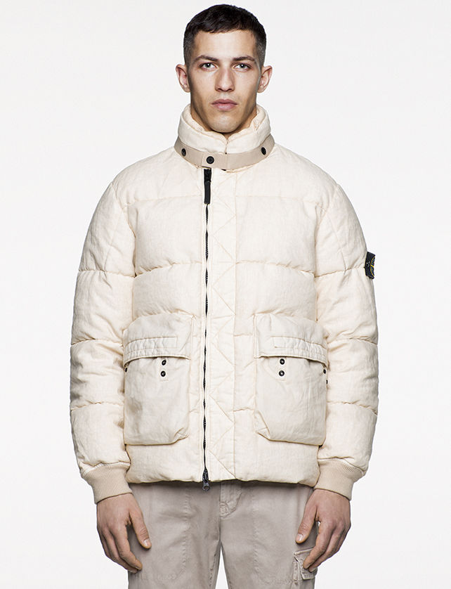 Model wearing white, quilted jacket with horizontal bellows pockets and off center zipper fastening.