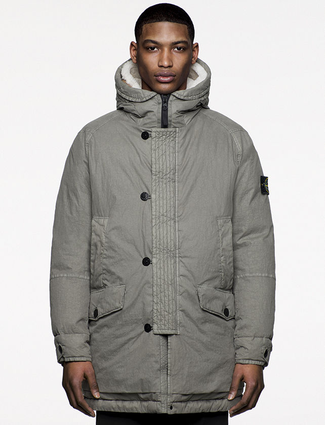 Model wearing gray, hooded, quilted jacket with flap and snap horizontal pockets, vertical welt pockets at chest and zipper and button fastening.