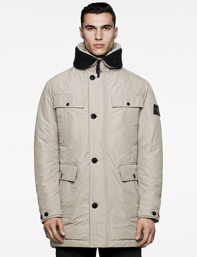 Model wearing off white, quilted jacket with a black turned down collar, four flap and snap horizontal pockets and zipper and button fastening.