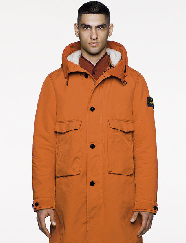 Model wearing orange parka with hood, two large bellows pockets and concealed zipper and button fastening.