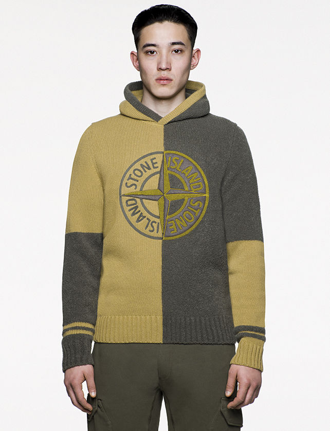 Model wearing green and mustard, hooded sweater with the Stone Island Compass logo at chest.
