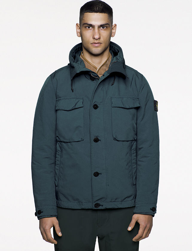 Model wearing blue jacket with stand up collar, vertical welt pockets, horizontal flap pockets at chest and zipper and button closure.