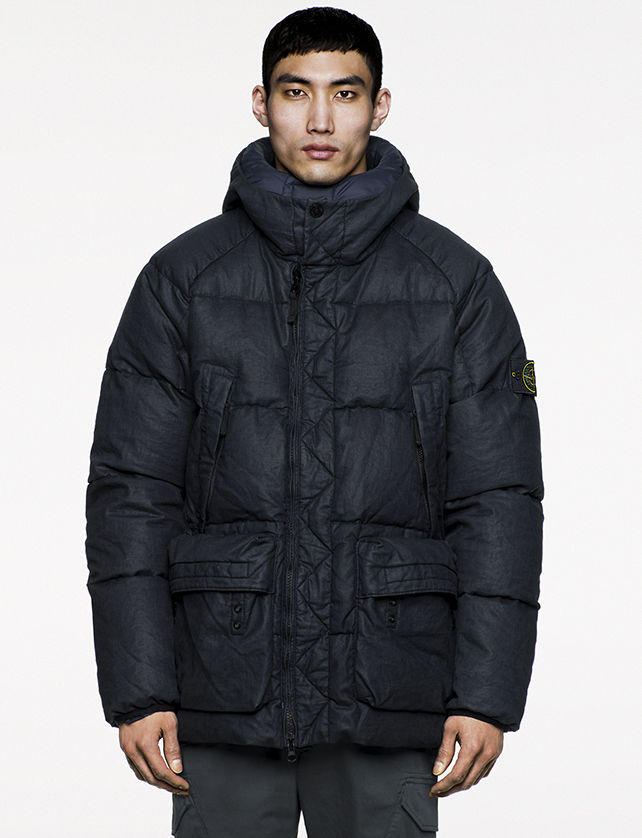 Model wearing oversized, navy, quilted jacket with chimney collar, four pockets and off center zipper closure.