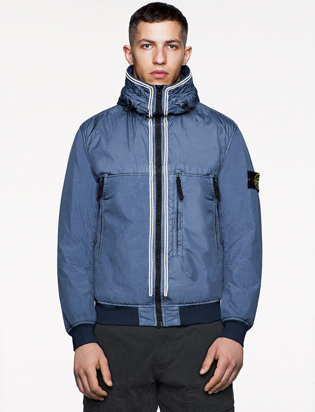 Model wearing blue bomber jacket with high collar, three vertical zipper pockets and zipper closure.