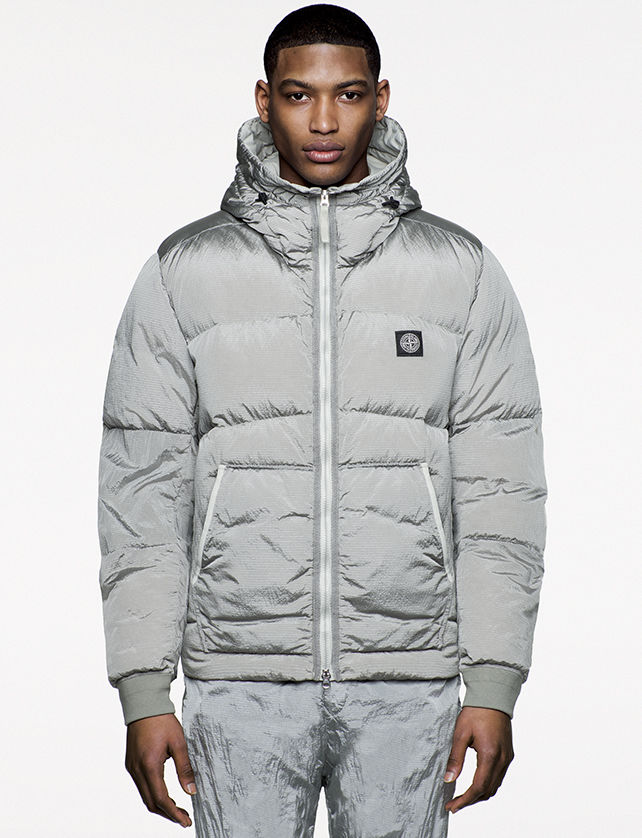 Model wearing shiny gray, quilted jacket with hood, diagonal pockets and zipper closure.