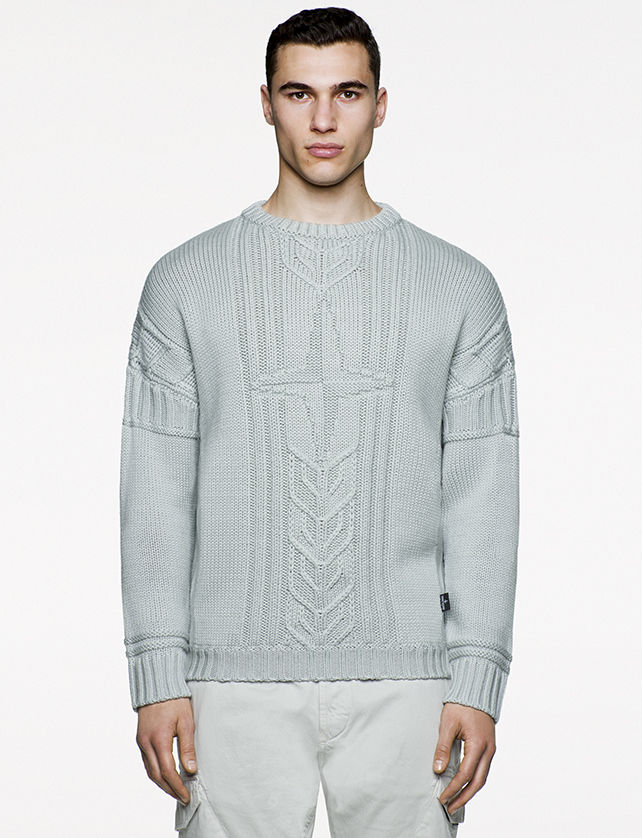 Model wearing gray knitted sweater with Stone Island logo at chest.