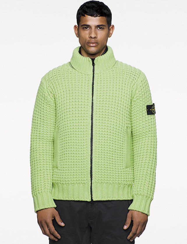 Model wearing green knitted cardigan with stand up collar, vertical pockets and black zipper fastening.