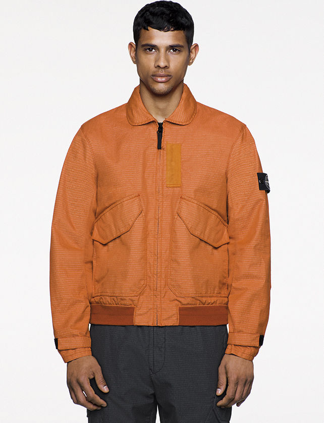 Model wearing orange bomber jacket with large, diagonal flap pockets and a zipper fastening.