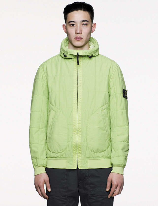 Model wearing green, quilted bomber jacket with stand up collar, diagonal pockets and zipper fastening.