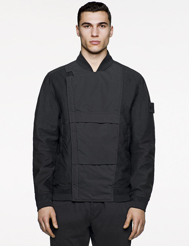 Model wearing black bomber jacket with a dark gray central panel and off center, concealed fastening.