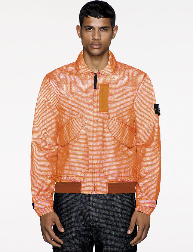 Model wearing orange bomber jacket in jacquard fabric.
