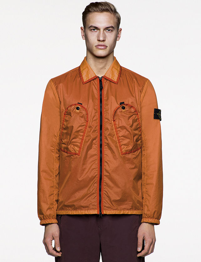 Model wearing two tone, orange bomber jacket with diagonal chest pockets and black zipper fastening.