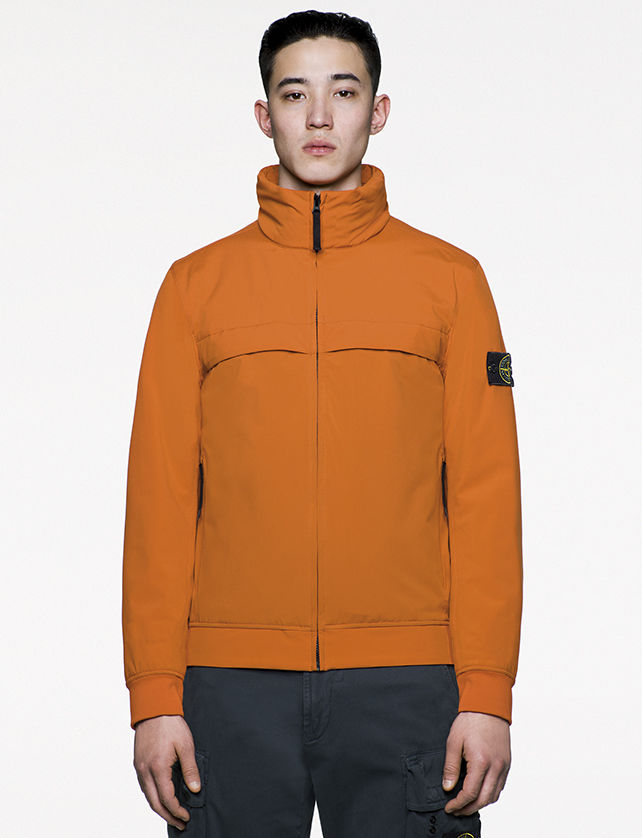Model wearing casual, orange jacket with chimney collar zipped up to chin.