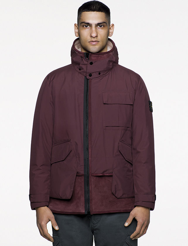 Model wearing maroon jacket with stand up collar, large diagonal bellows pockets and off center zipper fastening.