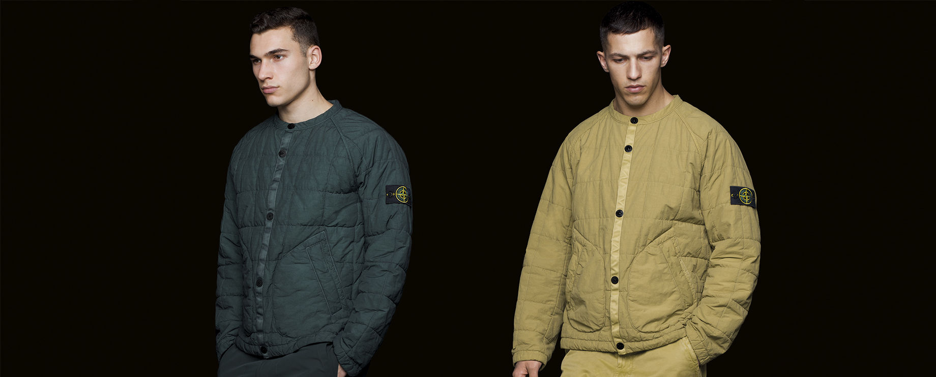 Two models wearing the same style bomber jacket, one in dark green and one in mustard yellow.