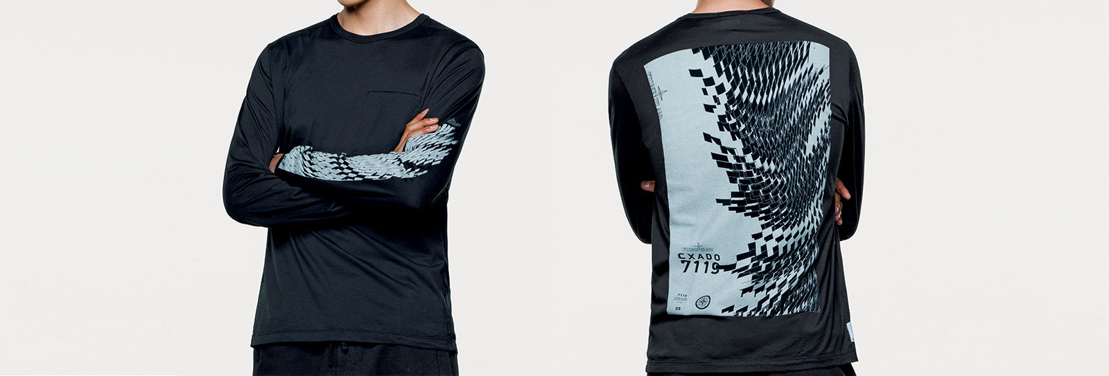 Model wearing dark colored long sleeve t shirt with graphics printed on left arm and back.