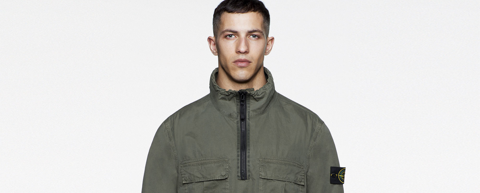 Close up of model in a sage green jacket with stand up collar, horizontal flap pockets at chest and zipper closure at chest.