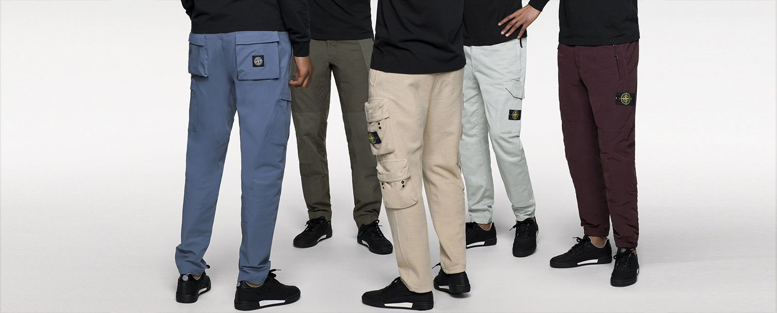 Five models wearing different styles of pants with different styles of pockets.