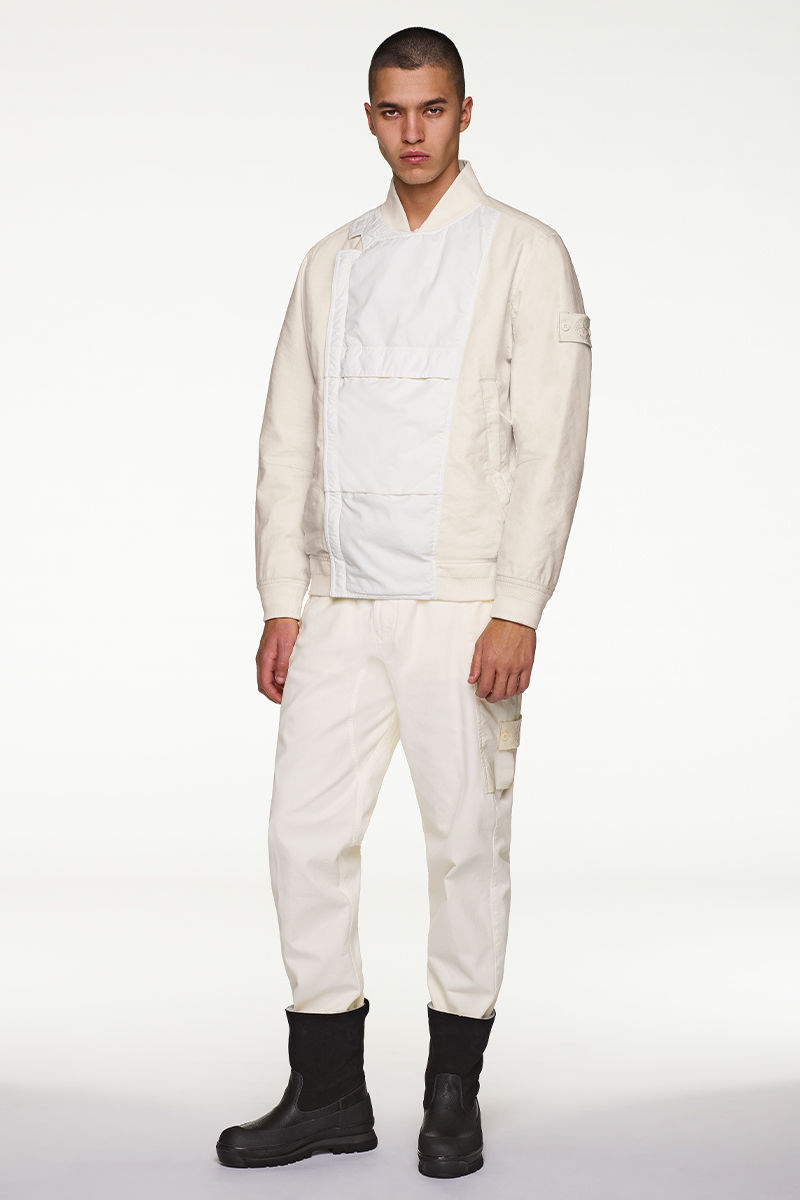 Model wearing white jacket with stand up collar, white pants and black boots.
