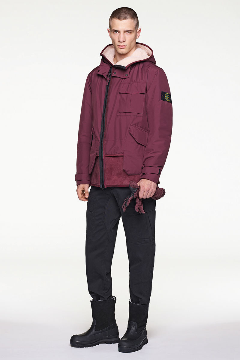 Front view of model in dark burgundy jacket, black pants and black boots.