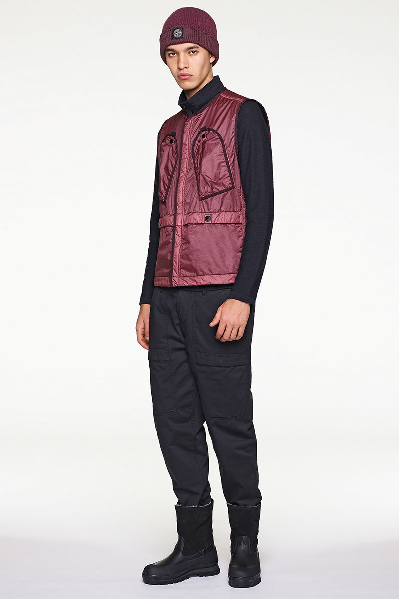 Front view of model in dark burgundy beanie and vest worn with black sweater, pants and calf length boots.