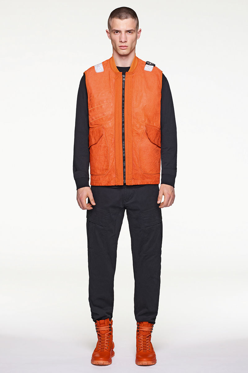 Model wearing orange vest, black sweater, black pants and orange high top sneakers.