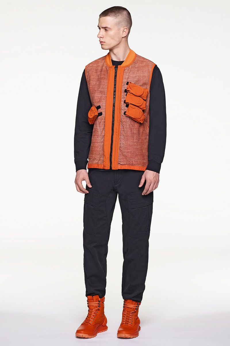 Model wearing orange vest with three diagonal chest pockets on left chest and one on lower right chest, black sweater, black pants and orange high top sneakers.