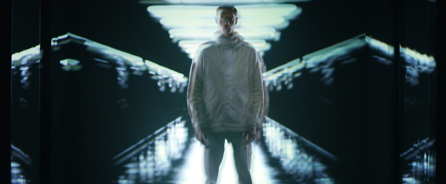 Model wearing off white hooded jacket standing in front of wall with video projection.
