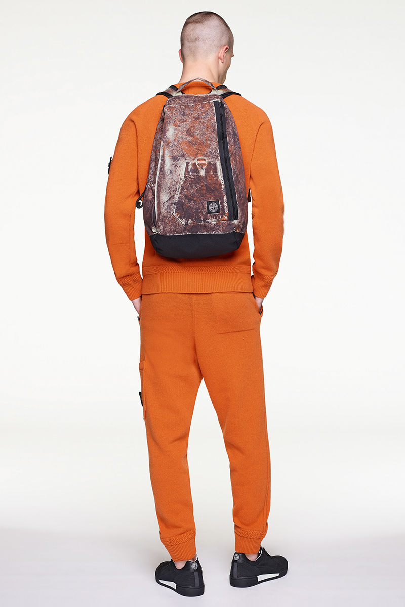 Back view of model wearing orange sweater with matching pants, black and white sneakers and multi colored backpack.
