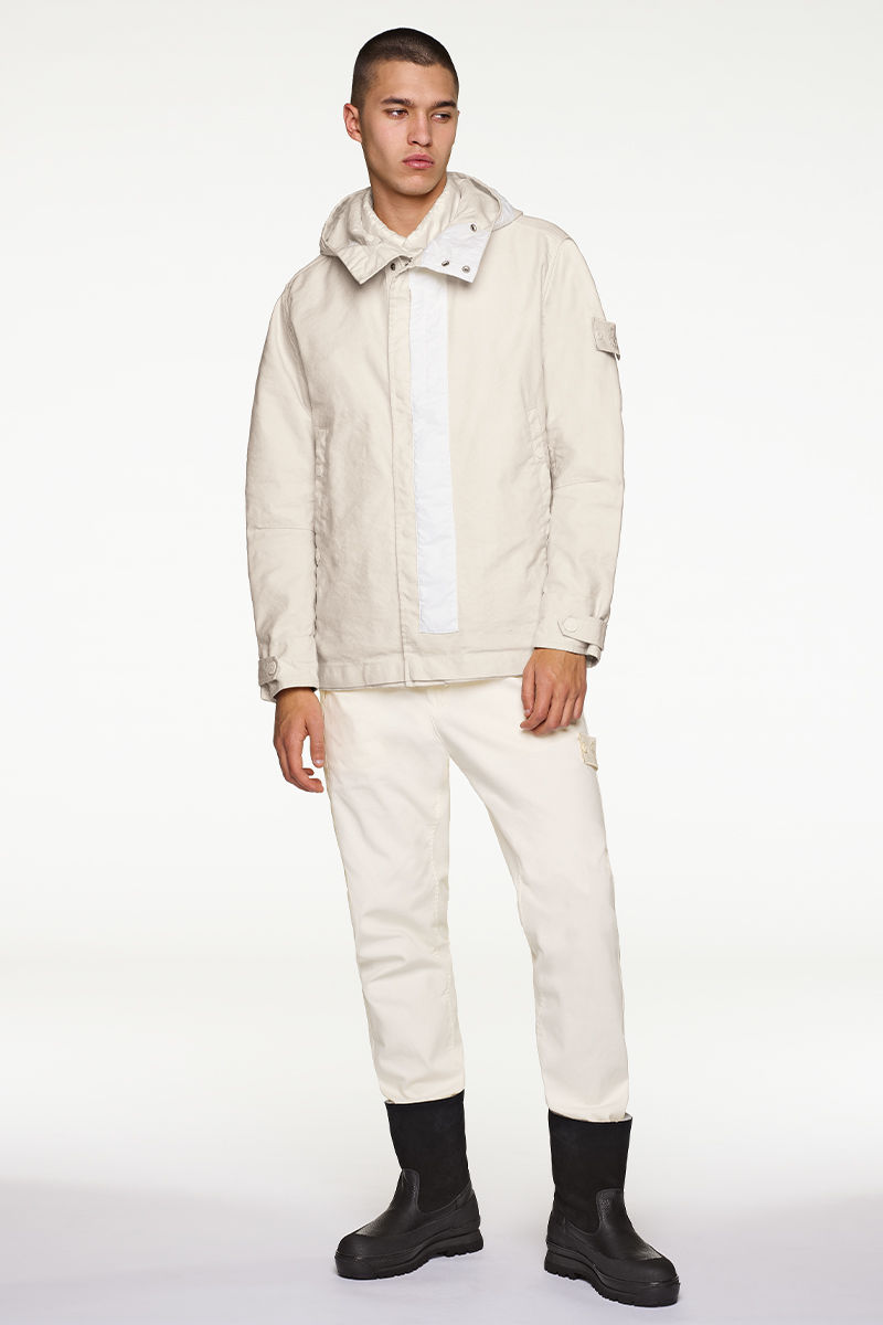 Model wearing white, hooded jacket, white pants and black boots.